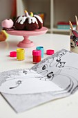 Pots of paints and colouring book on table in child's bedroom; decorative, fabric cakes on plastic cake stand
