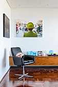 Retro swivel armchair in front of Vietnamese poster and amusing 70s ornaments on sideboard
