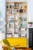 Shelving in niche above bright yellow drawers as modern element between rounded kitchen shelving and antique fireplace surround