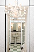 View though open, lattice, double doors into bathroom with pedestal basin; white, wallpapered, fitted cupboards and chandelier in foreground