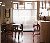 Open-plan kitchen with dining table & bar stools at kitchen counter