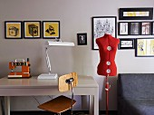 Interior with gallery of pictures, tailor's dummy & table with sewing machine and table lamp
