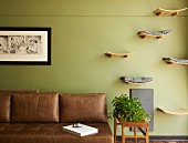 Hand-crafted wooden shelves as sleeping areas for cats next to leather couch in living room