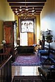 Antikmöbel unterschiedlicher Stilrichtung, Orientteppich und Kronleuchter in schmalem, gelb getöntem Raum