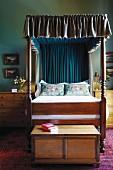 Holzbett mit gerüschtem Baldachin, flankiert von Nachttischkommoden und Truhe am Fussende
