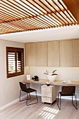 Simple fitted furniture in home office with slatted glass ceiling