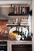 Cookery books and bottles on floating shelves & crockery on cast concrete base unit in kitchen