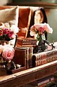 Antiquarische Bücher mit goldgeprägtem Ledereinband, antike Buchstütze und kleine Rosensträusse auf altem Holzregal