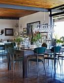 Filigrane Metallstühle um rustikalen Esstisch, darauf eine Sammlung Glasbehälter mit Pflanzen in schlichtem Wohnraum