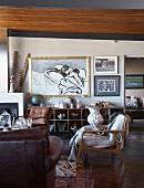 Wohnbereich mit verschiedenen Sesseln im 50er Jahre Stil, im Hintergrund moderne Malerei über offenem Regalschrank an Wand