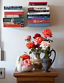 Bouquets of roses in metal jugs and swan-shaped china vase on half-height cabinet below stacked books on minimalist, floating bookshelves