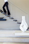 Floating staircase with steps protruding from wall and minimalist handrail
