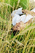 Man lying in tall grass with eyes closed