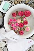 Schwimmende Rosenblüten in alter Emailleschüssel mit weißem Leinenhandtuch und Seifenschale auf einer Kiesfläche arrangiert