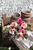 Rosenstrauss mit gestreiftem Geschirrtuch und alten Blumentöpfen in einfacher Holzkiste
