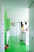 Woman in open-plan white, designer kitchen with green floor