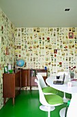 White shell chairs with green seat cushions at white dining table and 50s-style corner sideboard against patterned wallpaper