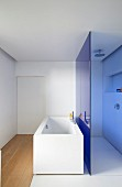 Blue glass partition between free-standing bathtub and shower area in designer bathroom
