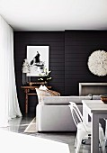 Modern living-dining area in white in front of black wood-panelled wall with white artworks above fireplace and small, antique table