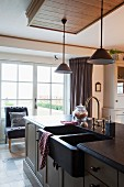 Küchentheke mit hell lackierten Fronten im Shakerstil, dunklem Doppelspülbecken und messingfarbener Retro-Armatur