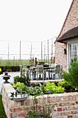 Grosser Essplatz auf Terrasse vor traditionellem Backsteinhaus mit Spalierbaum-Zaun und gemauertem Pflanzbeet mit Salatköpfen