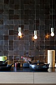 Small, simple pendant lamps in front of elegant charcoal wall tiles in architect-designed kitchen