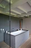 In freistehenden, grauen Steinkubus eingebaute Wanne im Designerbad mit historischer Holzdecke