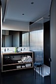 Designer washstand with integrated twin sinks in open-fronted base unit next to glazed shower area