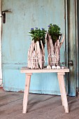 Originelle Blumentöpfe aus verschnürtem, hellem Treibholz auf Holzhocker vor Vintage Tür