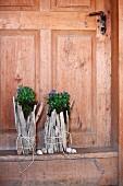 Originelle Blumentöpfe aus verschnürtem, hellem Treibholz vor alter Landhaustür