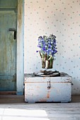 Glass vase of delphiniums and driftwood arranged on vintage trunk against wallpaper with delicate pattern