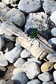 Lovingly wrapped gift decorated with driftwood and forget-me-nots on pebbly beach