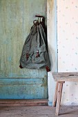 Rustic duffel bag hanging from handle of old country-house door