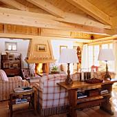Elegantes Chalet-Wohnzimmer mit Kaminfeuer und massiver Dachbalkenkonstuktion