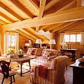 Elegantes Chalet-Wohnzimmer mit massiver Dachbalkenkonstuktion und Antikmöbeln
