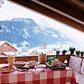 Table set for simple lunch in loggia of chalet with view of snowy mountain landscape