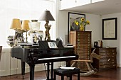 Antique table lamps on grand piano in front of window next to antique chests of drawers