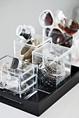 Small plexiglas boxes used to store jewellery and glasses on black tray