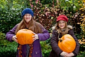 Two girls holding giant pumpkins in the garden