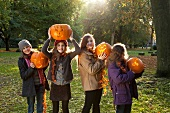 Four girls holding Halloween pumpkins in an autumnal park