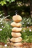 Aufgestapelte, runde Steine vor einer Wasserleitung im Garten