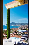 Blue and white striped sun lounger on terrace with climber-covered pillar; view over bay on Italian Riviera