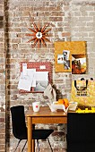 50s designer wall clock (Sunburst Clock) and pinboards covered in patterned fabrics decorating brick wall