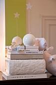 weiße Deko-Kugel-Kerzen mit Stern auf Bücherstapel und hellgrünem Farbstreifen an Wand