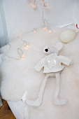 Detail of mattress with white soft toy on fur blanket and string of fairy lights