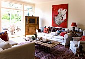 Wooden furnishings, sofas with scatter cushions and striking red painting in interior with view out onto sunny terrace