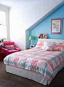 Child's attic bedroom with colourful, gingham bed linen and light blue wall