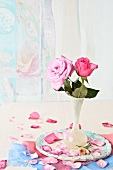Pink roses in a white flower vase on a ceramic plate