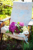 Lila und weisse Flieder auf einem alten Polsterstuhl im Garten