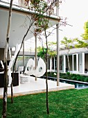 White chair hanging from roof of veranda alongside pool in courtyard of contemporary house